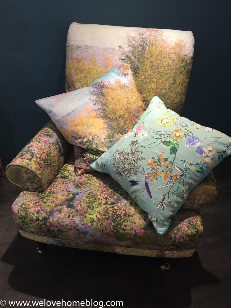 Look at this wonderful chair upholstered with a print by artist Monnet. Just lush isn't it? Then see how they have layered up the embroidered cushions.