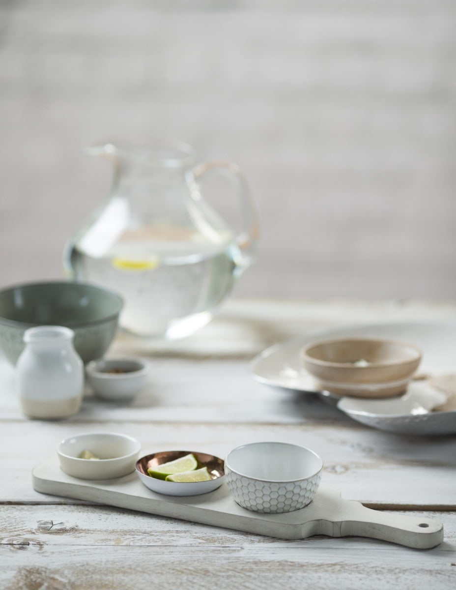 An image of a jug of water, modern bowls and rustic condiments on a faded white table