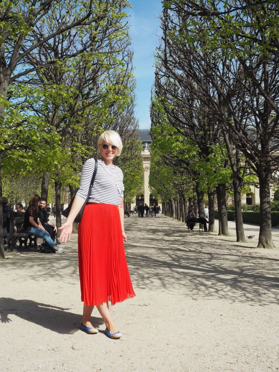 Maxine standing among some trees in Paris