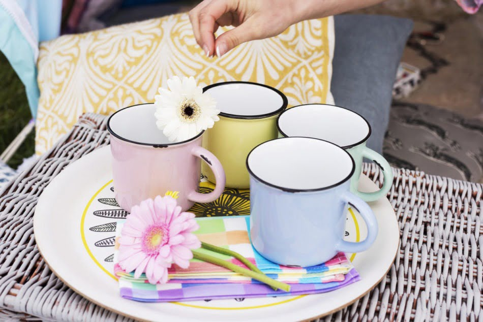 A flower being placed on top of some colourful mugs