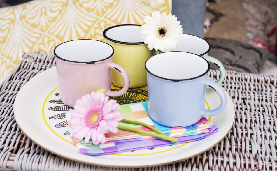 A flower resting on top of colourful mugs
