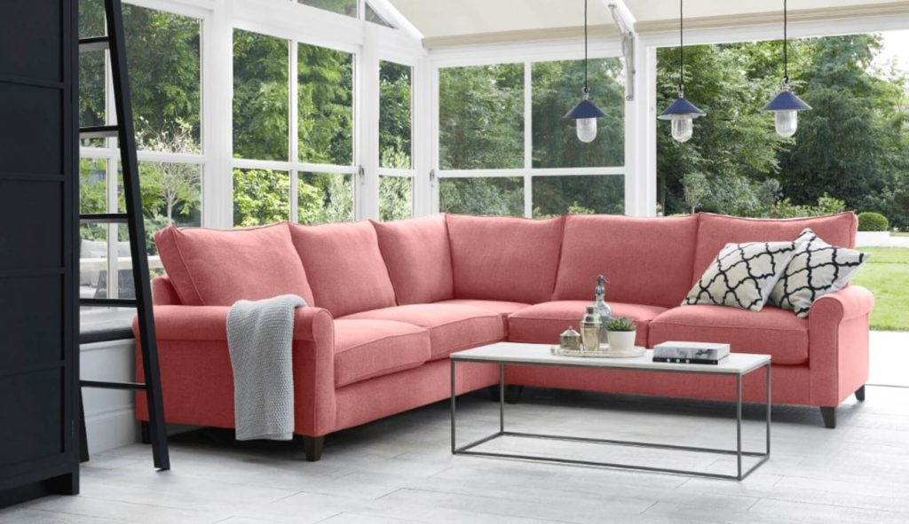 Discover these top 5 buyer's tips for buying a corner sofa by interior stylist and lifestyle blogger Maxine Brady from We Love Home Blog. pink corner sofa in fabric in conservatory / garden room / living room with lighting and coffee table.