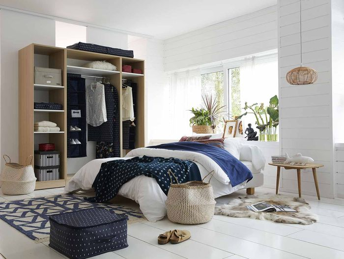 Discover how to tackle your bedroom clutter with these 6 stylish bedroom storage solutions for your home by interior stylist Maxine Brady. Blue bedroom with lots of clever storage ideas with white painted floorboards.