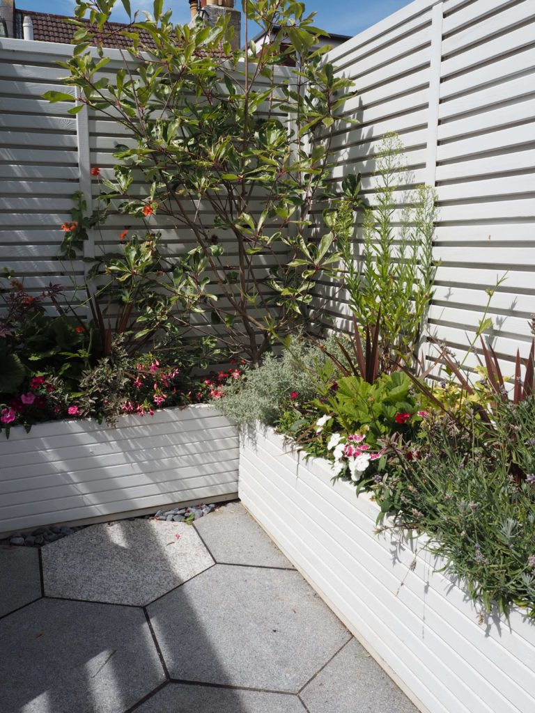 Enjoy Summer for longer and make the most of every ray of sunshine with these 8 ideas on how to create an outdoor garden room. From paint, to furniture to accessories - this post has got it covered.outdoor garden table, painted outdoor furniture, english garden. modern fencing,  paving