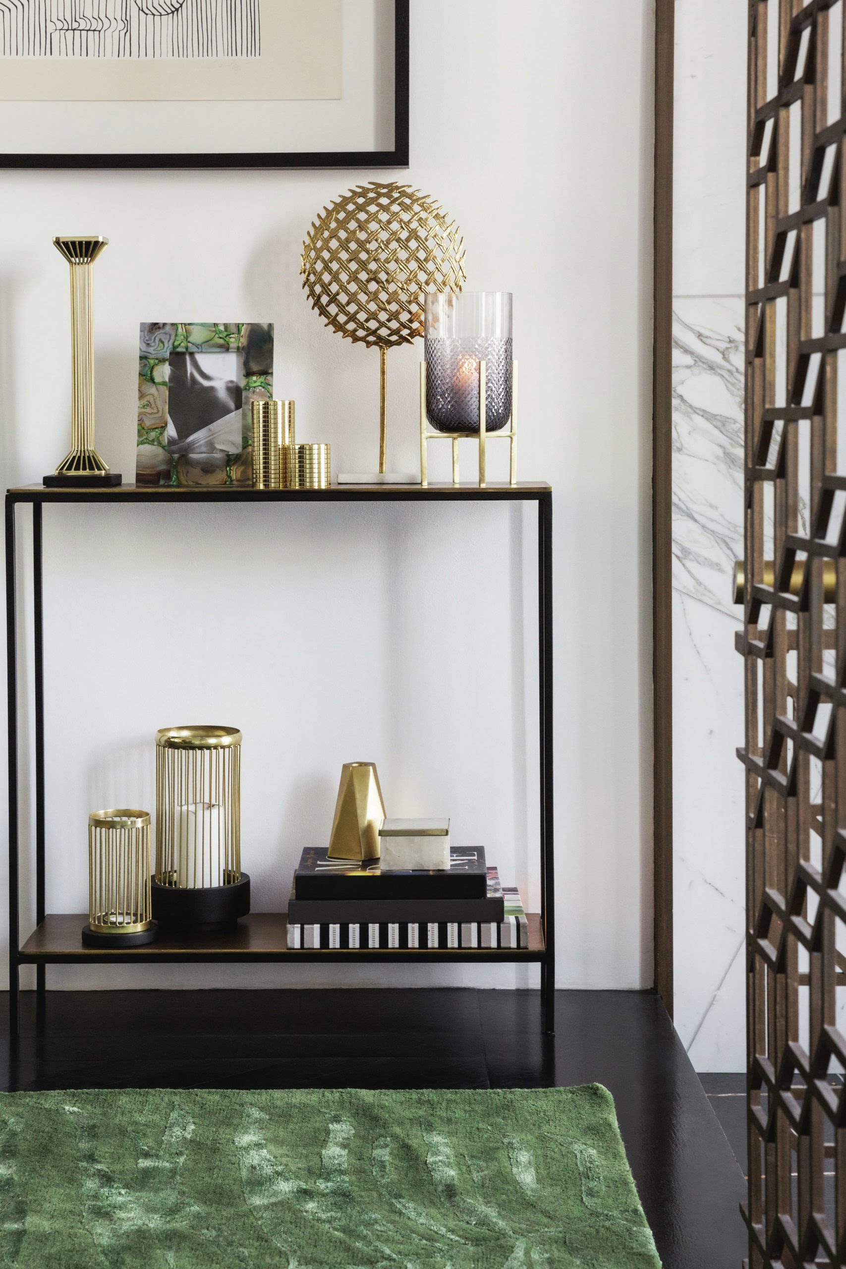small shelving unit with gold accessories and candles