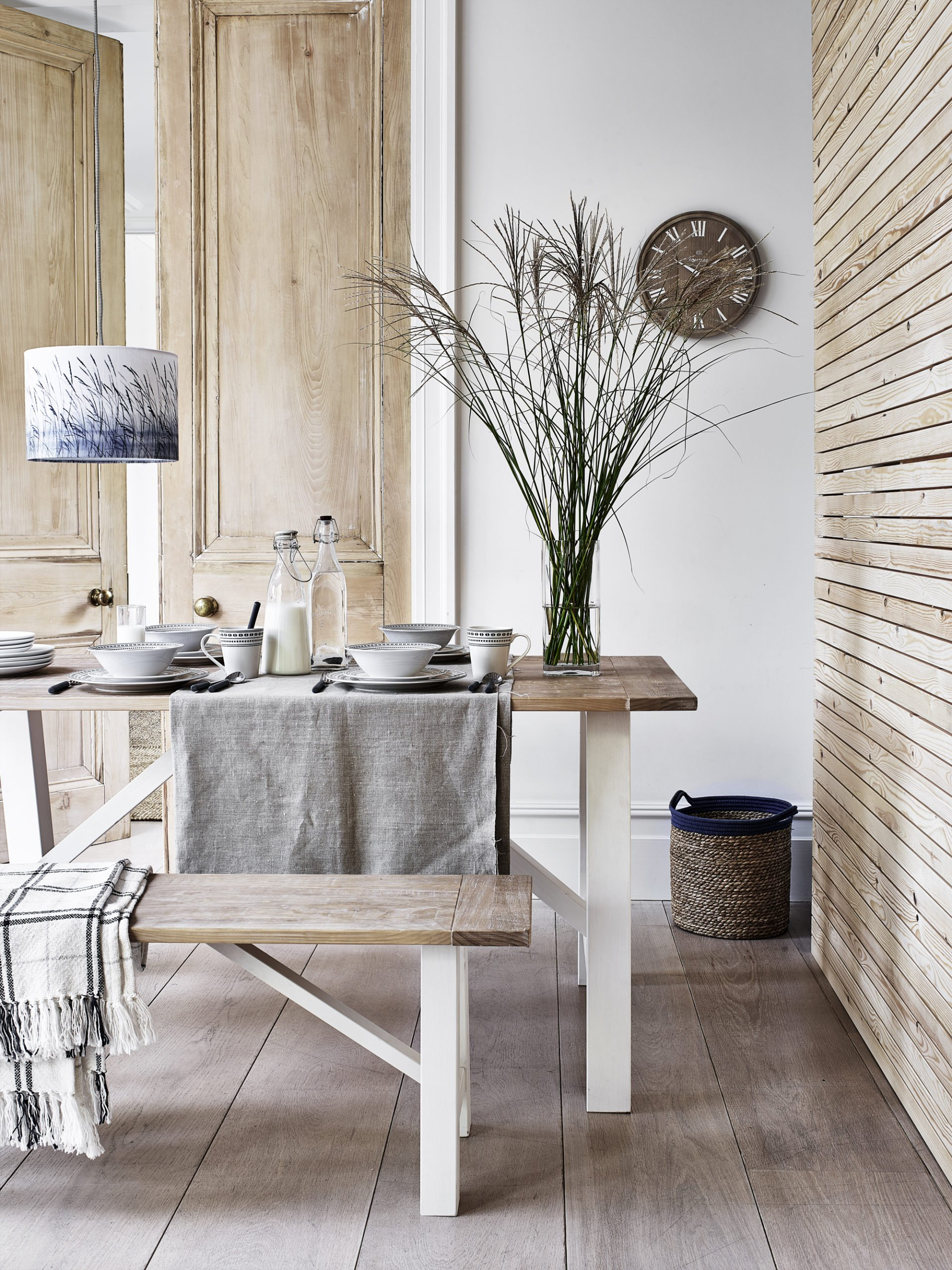 neutral rustic dining room with wooden table and bench - scandi style. Beach house.