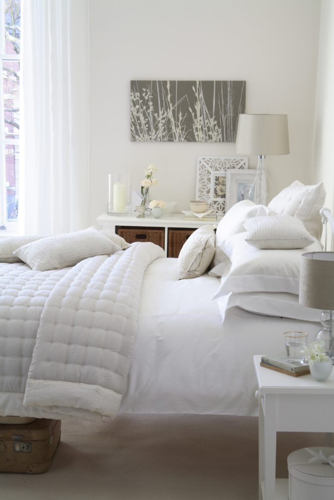 White bedroom with velvet quilt and scatter cushions shabby chic styling, vintgae suitcase with rattan storage by Interior Stylist Maxine Brady