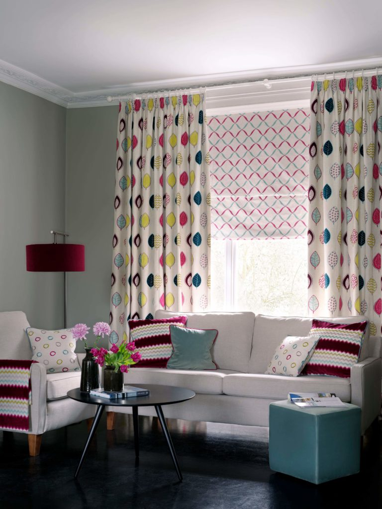 bold colourful window dressing in a living in blue, red and natural curtains and blinds