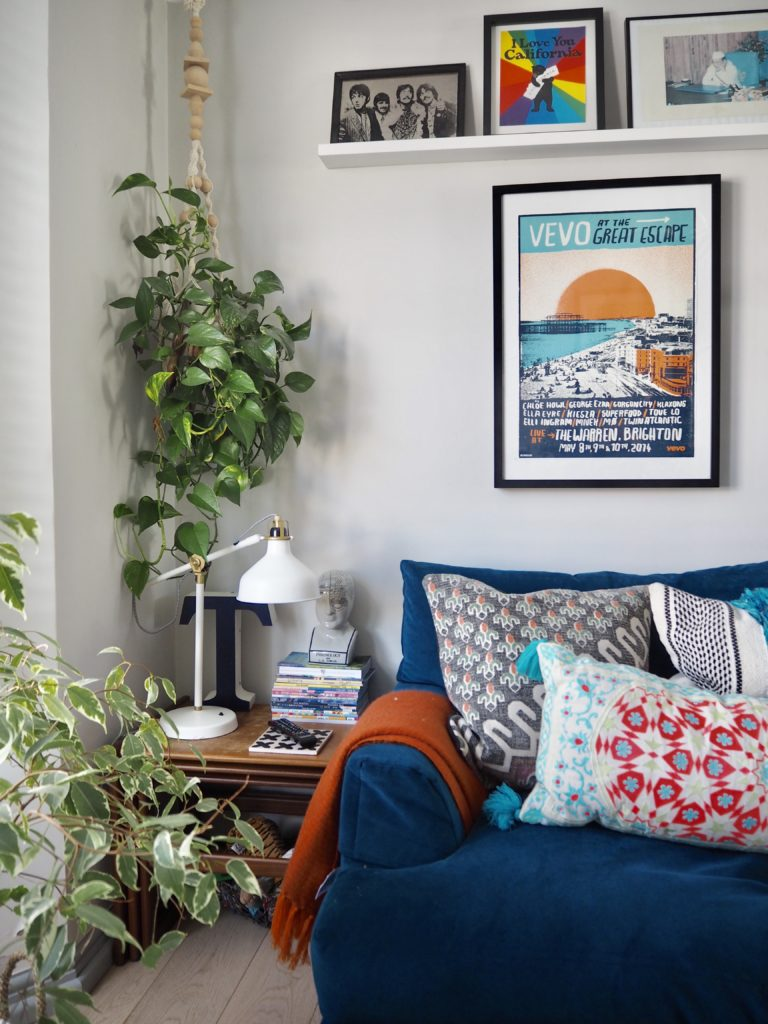 Blue velvet sofa with orange throw and gallery wall