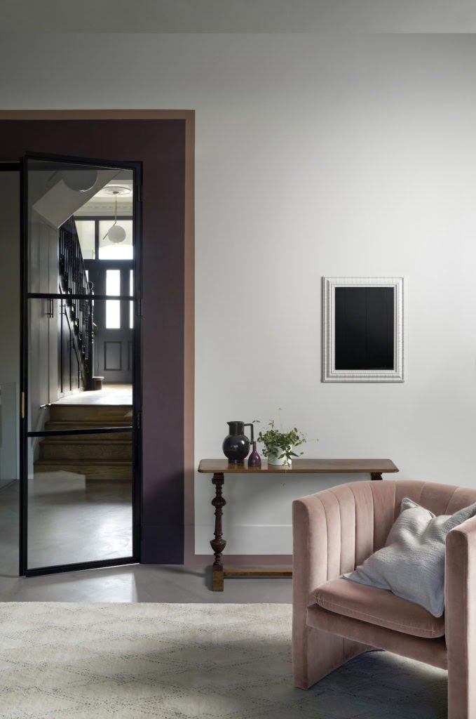 door lipstick painted living room with pink purple walls and velvet armchair