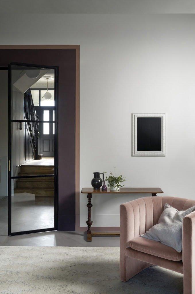 door lipstick painted living room with pink purple walls and velvet armchair