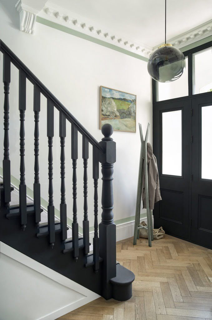 hallway with painted banister and black door