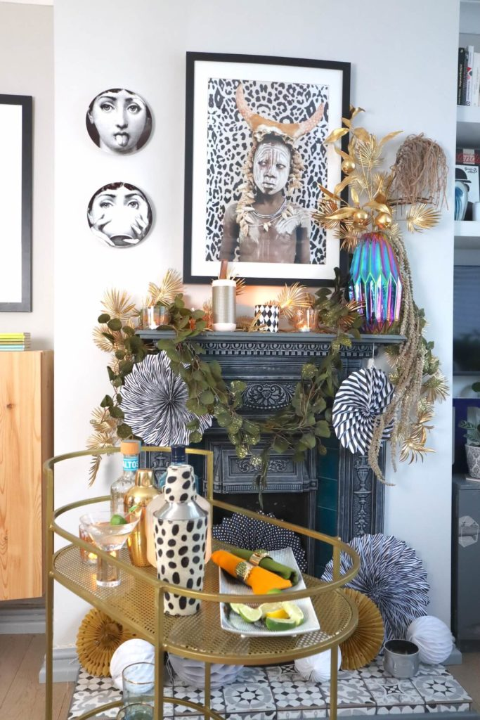 Fireplace & mantelpiece dressed with garland and paper decorations with cocktail gold trolley. black and white art. 7 cool Zoom Party Styling Ideas