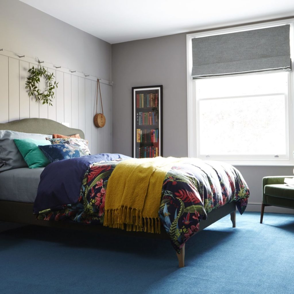 bedroom with blue carpet and painted panel wall, peg rail, green retro chair by Interior Stylist Maxine Brady